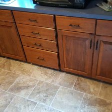 Kitchen cabinets refinished and tile floor installed on home remodeling project